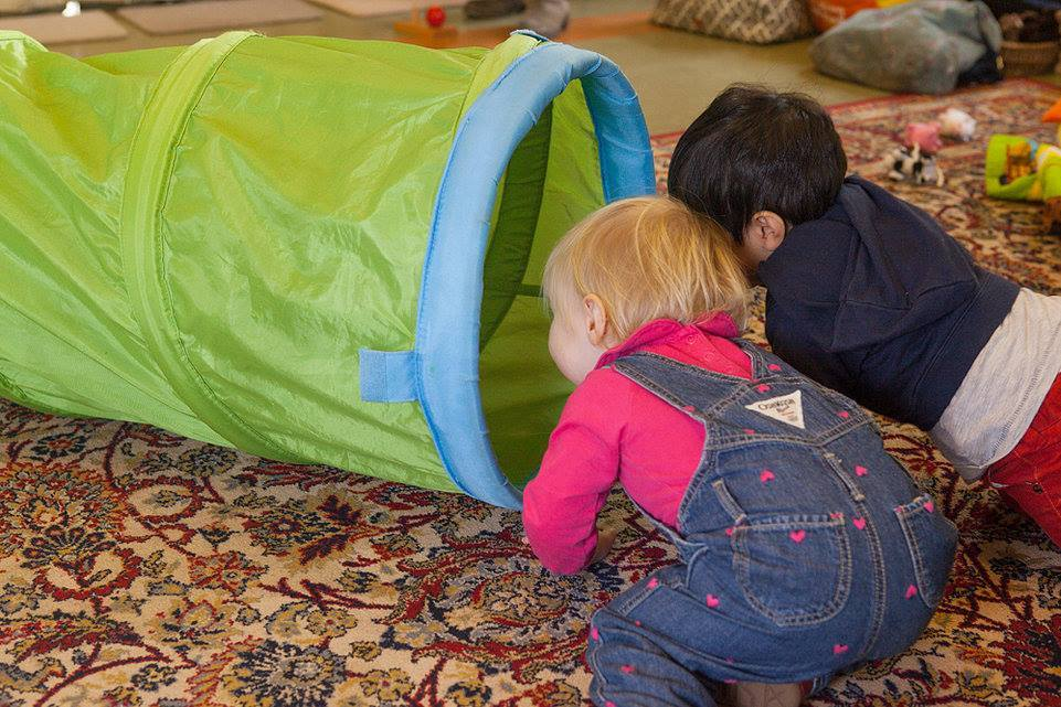 Toddler playing with tunnel Montessori